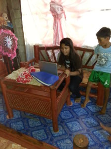 One of the children using the donated Chromebook that is shared by all the children for their school work.