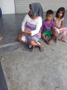 Woman begging with her two children
