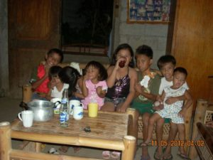 group of the children having something to eat and had a treat by all of them sharing the bottle of soda.