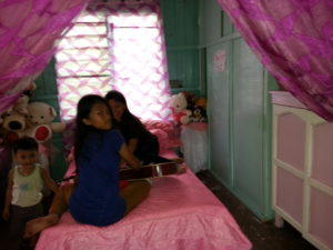 Babeselle and Mimi practicing the guitar. This is the twin bed that Inday and Babeselle share. In the background are many of the stuffed animals that have been sent to the children.